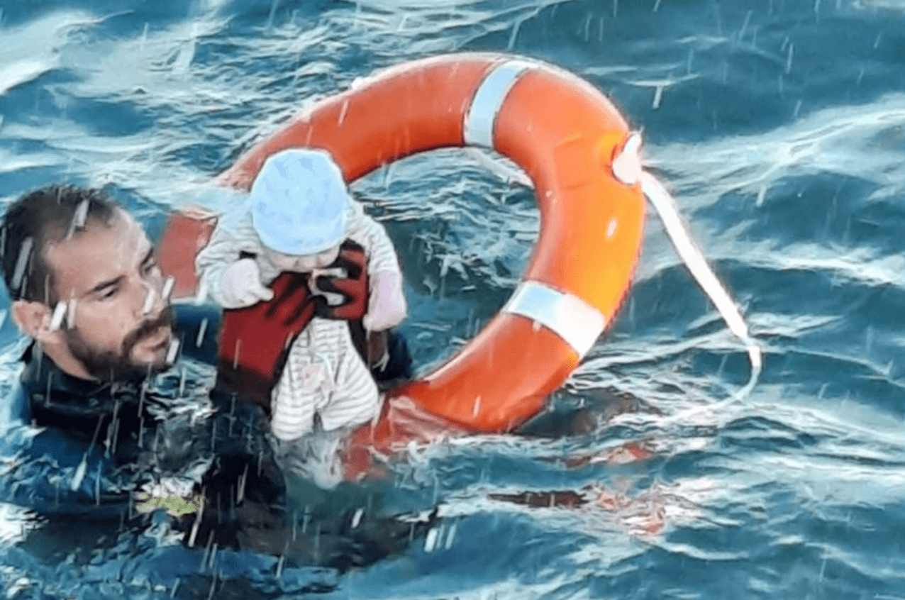 A Spanish Civil Guard diver rescuing a baby